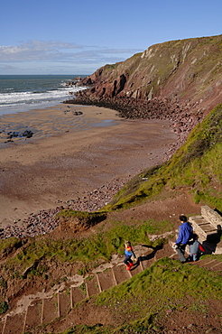 Mother and children going down steps to West Dale beach, Dale, Pembrokeshire, Wales, UK, Europe