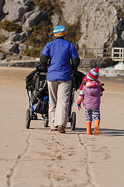 Mother pushing pushchair with children on beach, Broad Haven South, Stackpole, Pembrokeshire, Wales, UK, Europe
