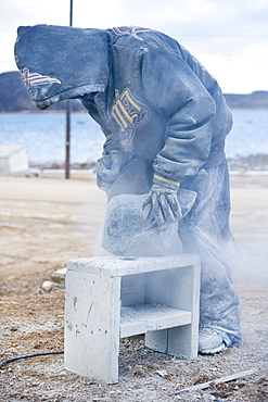 Local Inuit boy, carving from granite a polar bear. Cape Dorset, Baffin Island, Qikiqtaaluk, Nunavut, Canada, North America
