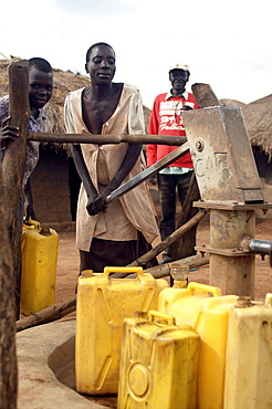 An IDP camp (internally displaced people) in Te-Tugu district of Northern Uganda has been created to accommodate the mass of Ugandan refugees fleeing the LRA (Lords Resistance Army) who are fighting the Ugandan government and its people.  Here, women are filling up water from a deep water well. Te-Tugu, Uganda, East Africa