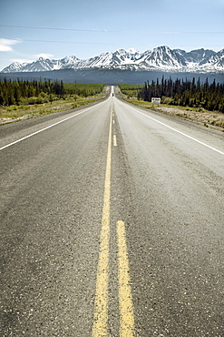 Long straight road leading to dramatic mountain range, snow capped mountains with forrest either side.  Clear blue sky in Sunny Alaska Interior. The Interior, Alaska, USA