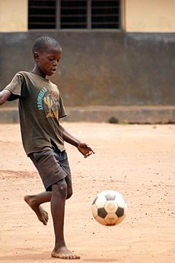 Young African boy playing football in the school yard.  Guly Town, northern Uganda. Gulu Town, Uganda, East Africa