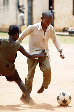 Two African boys committed to the tackle, playing football in the school yard.  Gulu Town, Northern Uganda. . Gulu Town, Uganda, East Africa