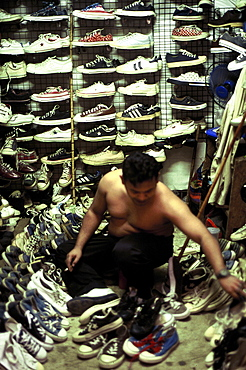 In cramped conditions at the Chatuchak Market, Bangkok, a Thai trader is searching through many pairs of 2nd hand trainers, some of which take pride of place covering the walls of his stall. Bangkok, Thailand
