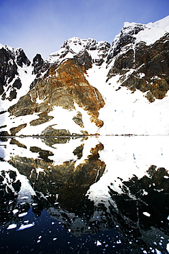 Reflections and snow covered mountains in Lemaire Channel in Antarctica.