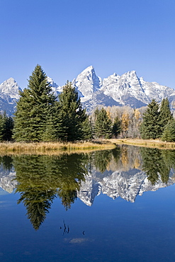 Reflected light on water from the Grand Teton Mountain Range, outside of Jackson Hole, Wyoming. This image was shot from the Schabawacker Landing on the snake river.