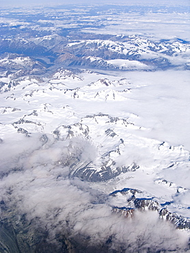 Aerial views of snow-capped mountains, ice fields, and glaciers on a commercial flight from Juneau to Anchorage Alaska, USA, Pacific Ocean