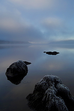 Loch Awe on a misty frosty morning, rocks in foreground, facing west.  Argyll, Scotland